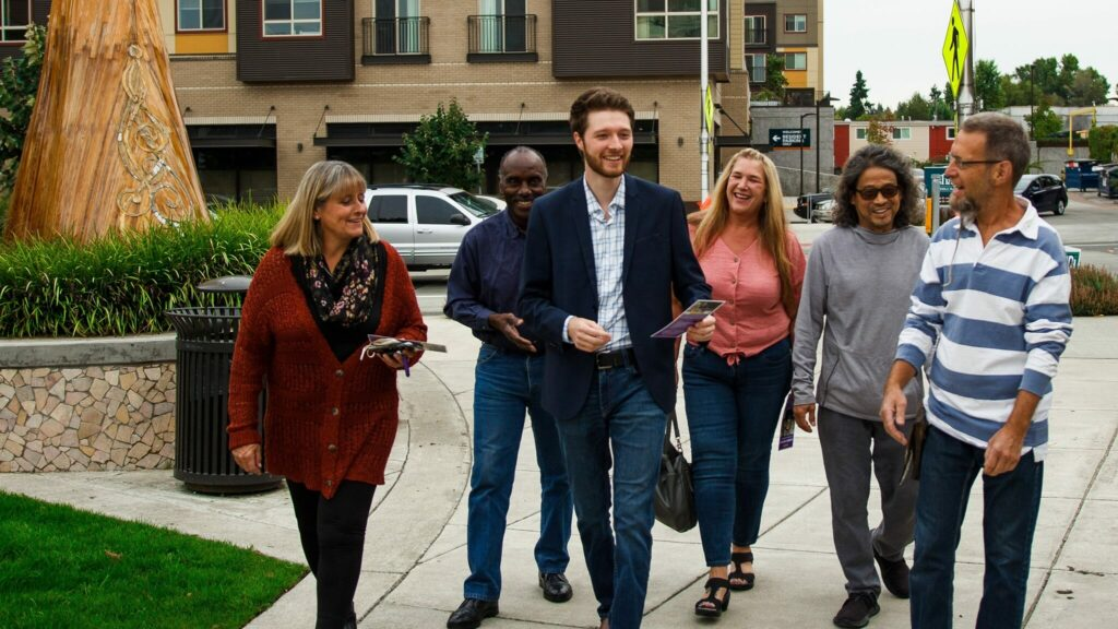 Photo of Armen Papyan, candidate for Tukwila City Council, walking with a group of 5 volunteers and supporters, along a street next to some green space. Armen is holding campaign literature.